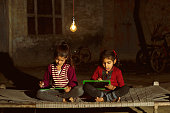 Two little Indian girls studying in single light bulb in the dark