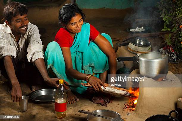 Rural, Indian husband and wife cooking dinner on clay stove
