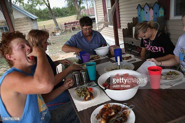 Rural Kansas farmer Darren Becker shares a homecooked dinner with his family on August 25 2012 in Logan Kansas Like many farmers affected by the...