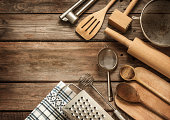 Rural kitchen utensils on vintage planked wood table from above - rustic background with free text space.