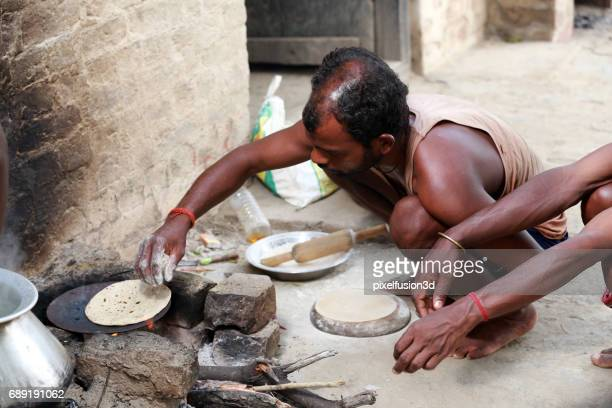 Rural men cooking in open  kitchen