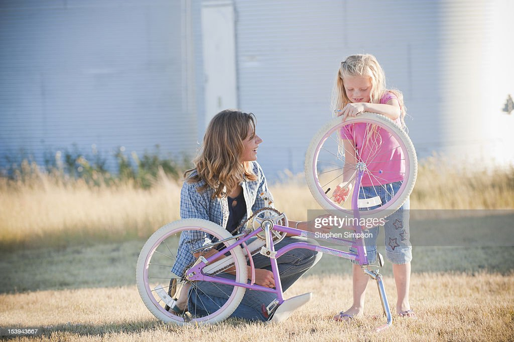 rural mom and daughter working on her bicycle : Stock Photo