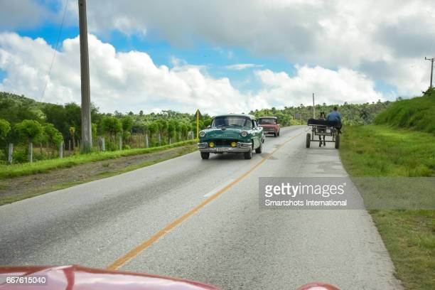 Rural scene with traditional vintage cars and horsedrawn transportation on country road in Valle de los Ingenios, Cuba