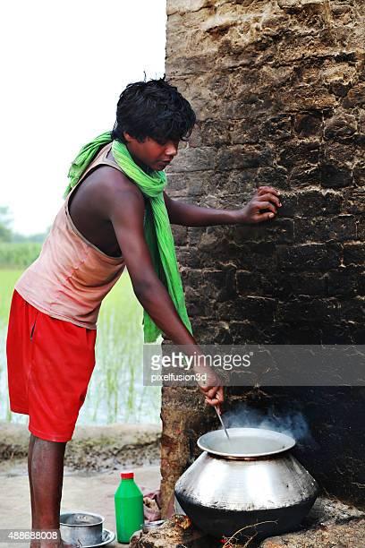 Rural Teenager Boy preparando la comida en la cocina a la vista
