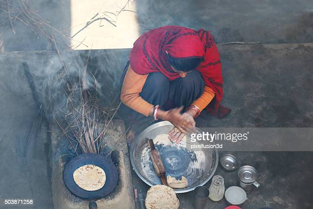 Rural women making chapatti on Wood burning stove (Chulha)