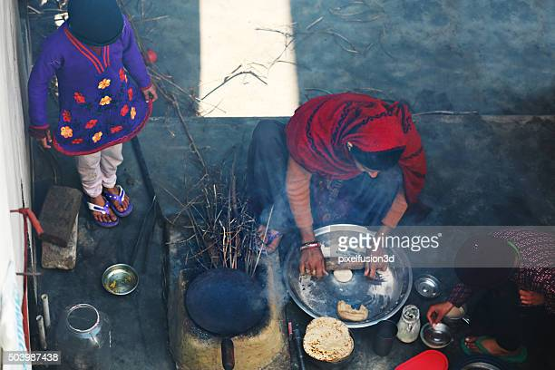 Rural women making chapatti on Wood burning stove (Chulha)