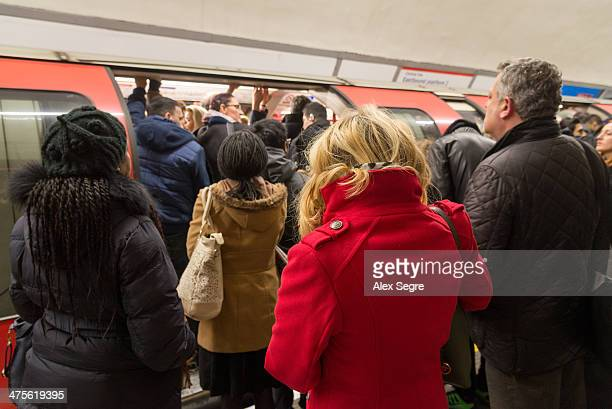 Rush hour commuters struggling to board crowded London Underground train UK
