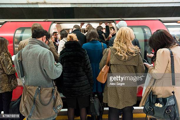 Rush hour commuters trying to get on overcrowded London Underground train UK