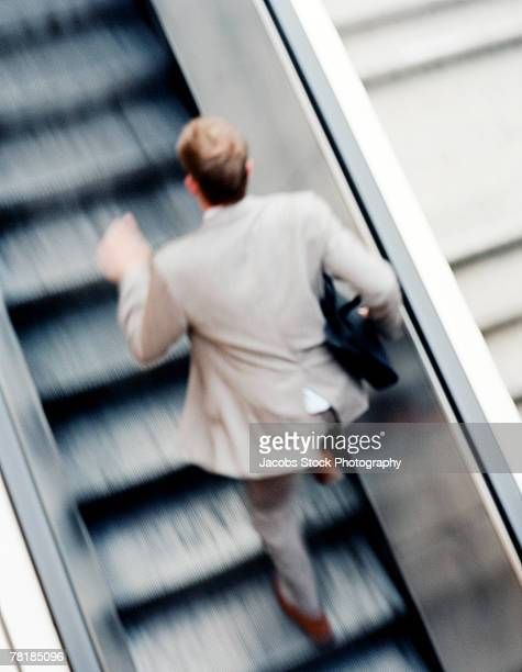 Rushing businessman running up an escalator
