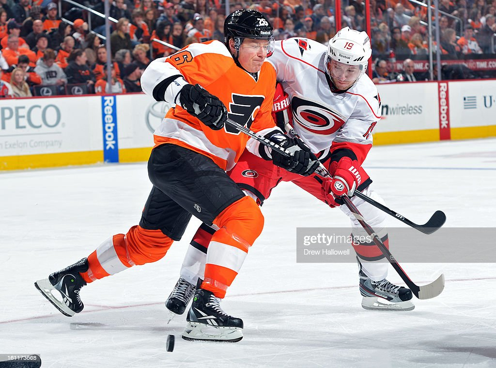 Ruslan Fedotenko #26 of the Philadelphia Flyers and Jiri Tlusty #19 of the Carolina Hurricanes fight for the puck at the Wells Fargo Center on February 9, 2013 in Philadelphia, Pennsylvania. The Flyers won 4-3 in overtime.