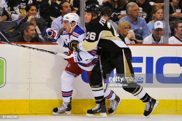 Ruslan Fedotenko of the Pittsburgh Penguins checks Matt Gilroy of the New York Rangers on October 2 2009 at Mellon Arena in Pittsburgh Pennsylvania