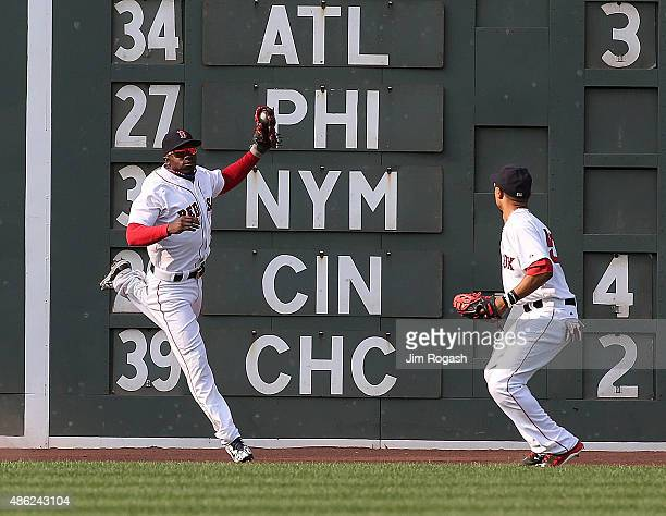 Rusney Castillo of the Boston Red Sox and Mookie Betts chase a ball hit off the wall by Chris Young of the New York Yankees in the second inning at...