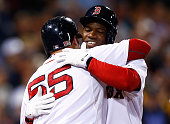 Rusney Castillo of the Boston Red Sox is hugged by teammate Christian Vazquez after hitting a threerun home run in the third inning against the Tampa...