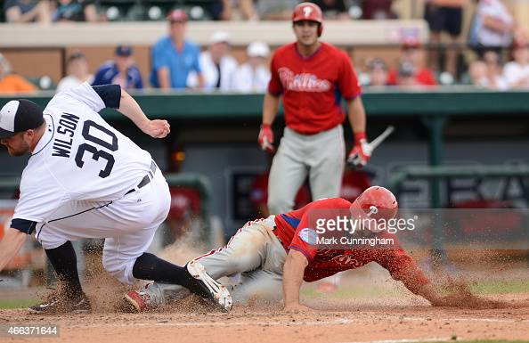 Russ Canzler of the Philadelphia Phillies slides safely into home ahead of the tag by Alex Wilson of the Detroit Tigers with what would turn out to...