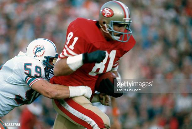 Russ Francis of the San Francisco 49ers gets wrapped up from behind Bob Brudzinski 59 of the Miami Dolphins in Super Bowl XIX on January 20 1985 at...
