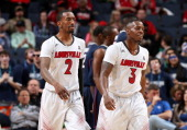 Russ Smith and Chris Jones of the Louisville Cardinals walk towards the bench against the Connecticut Huskies during the Championship of the American...