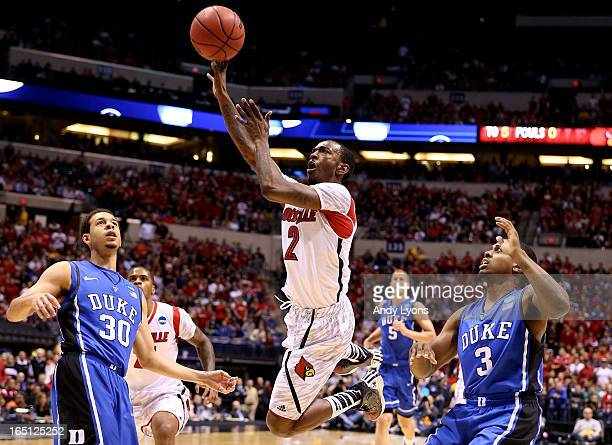 Russ Smith of the Louisville Cardinals drives for a shot attempt in the firts half against Seth Curry and Tyler Thornton of the Duke Blue Devils...