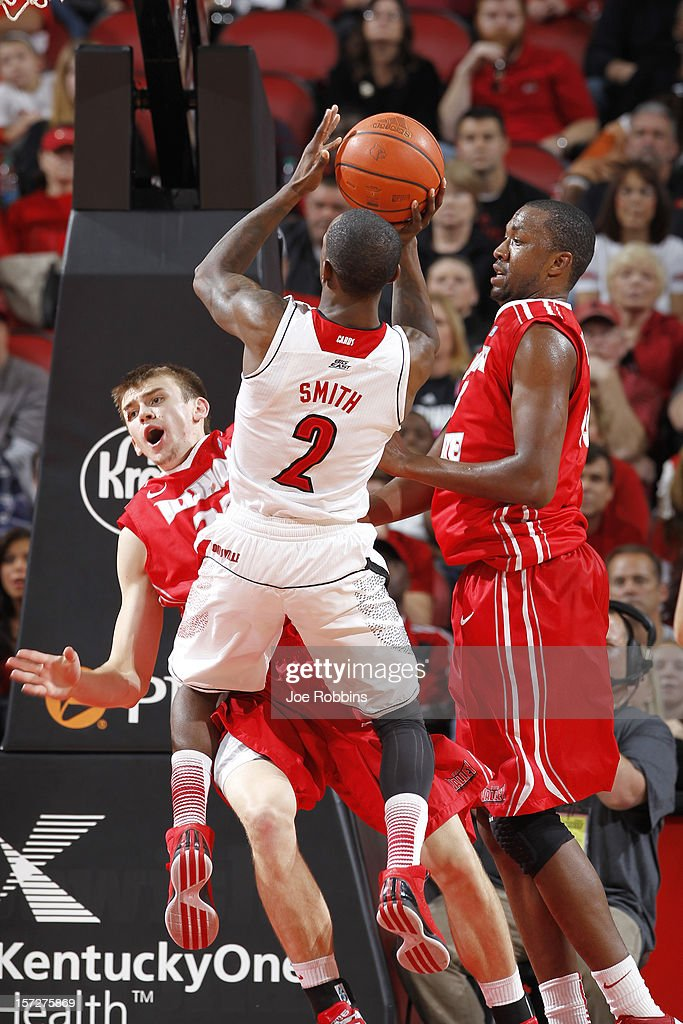Russ Smith #2 of the Louisville Cardinals drives to the basket against Jon Ekey #22 and John Wilkins #13 of the Illinois State Redbirds during the game at KFC Yum! Center on December 1, 2012 in Louisville, Kentucky. Louisville won 69-66.