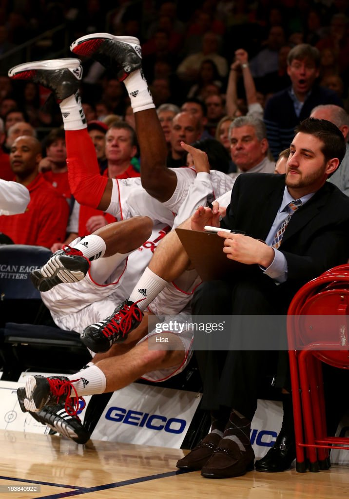 Russ Smith #2 of the Louisville Cardinals falls over a teammate on the bench out of bounds in the first half against the Syracuse Orange during the final of the Big East Men's Basketball Tournament at Madison Square Garden on March 16, 2013 in New York City.