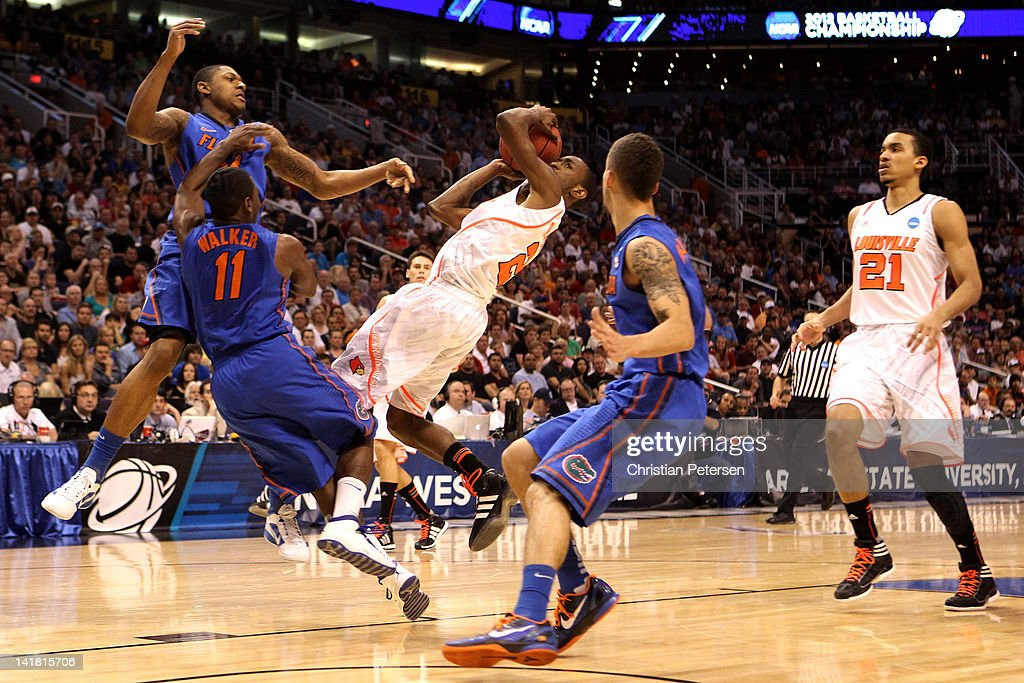 Russ Smith of the Louisville Cardinals goes up for a shot between Bradley Beal Erving Walker and Scottie Wilbekin of the Florida Gators in the second...