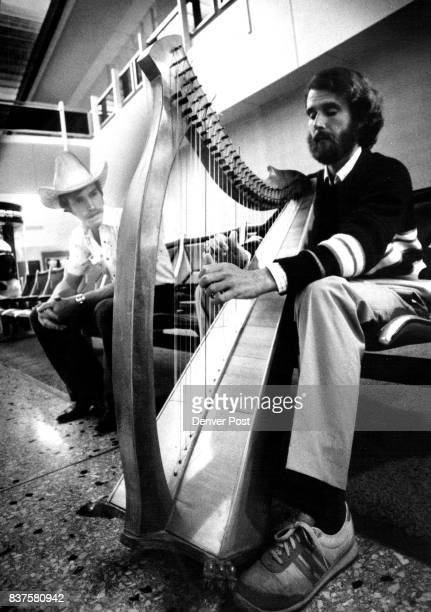 Russ Stevralta en route to Dallas plays Irish harp Dan Rieple another traveler delayed at Stapleton listens to music Credit The Denver Post