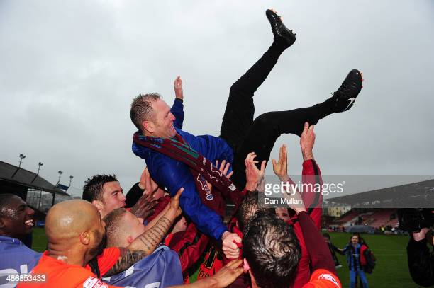 Russ Wilcox Manager of Scunthorpe United is hoisted aloft by his players following his sides promotion to League One after the Sky Bet League Two...