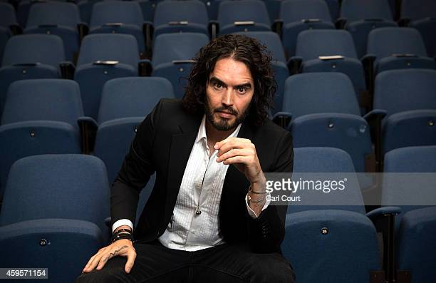 Russell Brand poses for photographs as he arrives to deliver The Reading Agency Lecture at The Institute of Education on November 25 2014 in London...