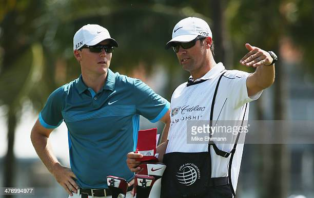 Russell Henley chats with his caddie Adam Hayes during the first round of the World Golf ChampionshipsCadillac Championship at Trump National Doral...