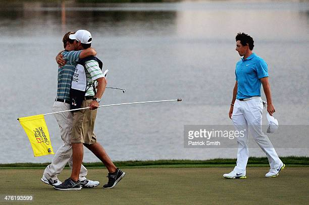 Russell Henley reacts with his caddie after winning a fourway playoff hole to defeat Rory McIlroy of Northern Ireland Russell Knox and Ryan Palmer to...