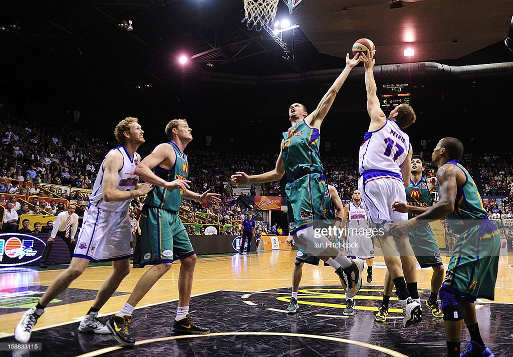 Russell Hinder of the Crocodiles contests the ball with Anthony Petrie of the 36ers during the round 12 NBL match between the Townsville Crocodiles and the Adelaide 36ers at Townsville Entertainment Centre on December 31, 2012 in Townsville, Australia.