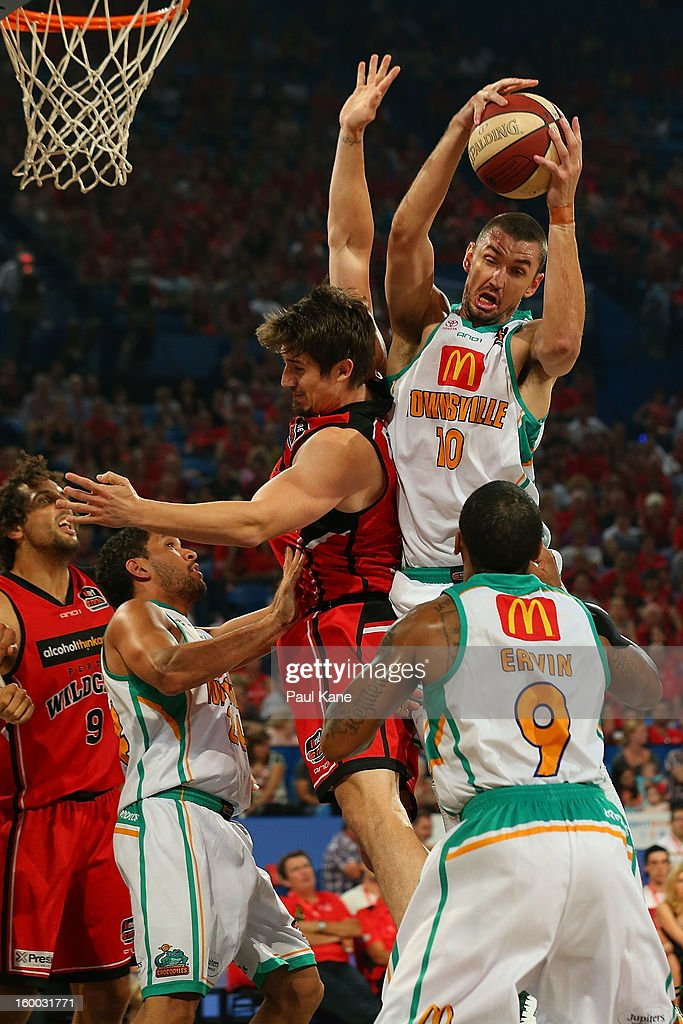Russell Hinder of the Crocodiles rebounds against Greg Hire of the Wildcats during the round 16 NBL match between the Perth Wildcats and the Townsville Crocodiles at Perth Arena on January 25, 2013 in Perth, Australia.