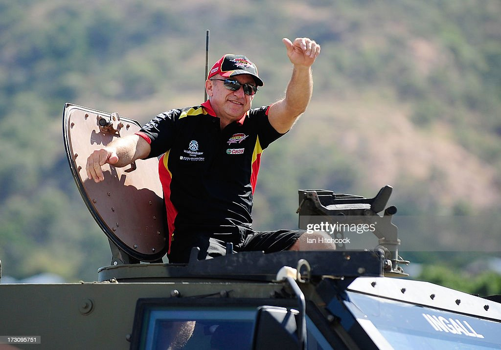 Russell Ingall who drives the #226 Supercheap Auto Racing Holden waves to the crowd from an Australian Army Bushmaster amoured vehicle during the drivers parade before race 21 of the Townsville 400, which is round seven of the V8 Supercar Championship Series at Reid Park on July 7, 2013 in Townsville, Australia.