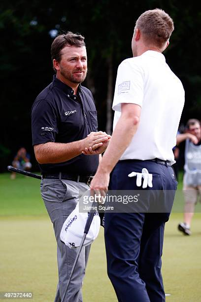 Russell Knox of Scotland congratulates Graeme McDowell of Northern Ireland on the 18th hole after winning the three man playoff in the final round of...