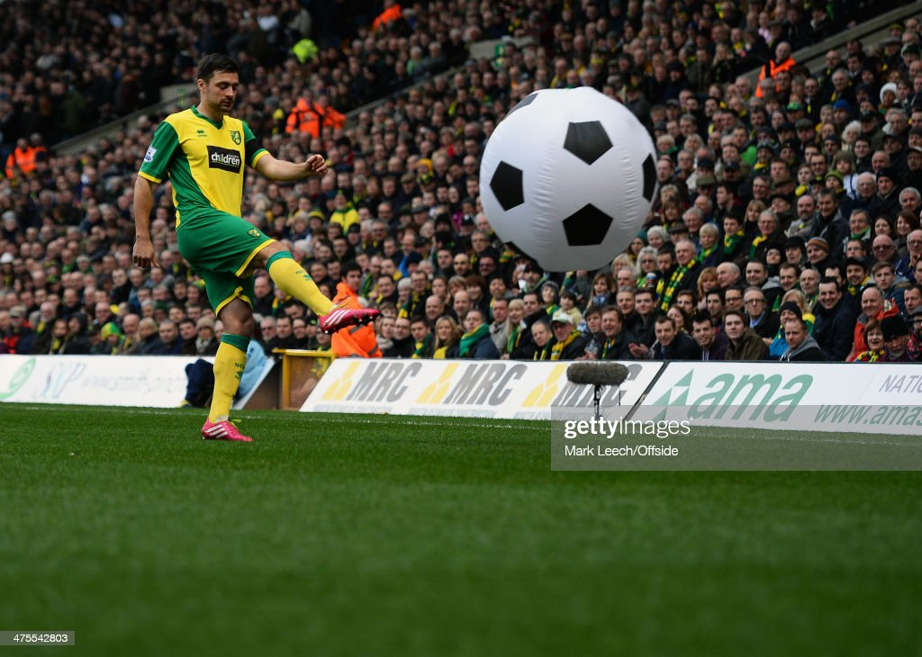 <a gi-track='captionPersonalityLinkClicked' href=/galleries/search?phrase=Russell+Martin+-+Soccer+Player&family=editorial&specificpeople=13764026 ng-click='$event.stopPropagation()'>Russell Martin</a> of Norwich City clears a giant football from the pitch during the Premier League match between Norwich and Tottenham Hotspur at Carrow Road on February 23, 2014 in Norwich , England.