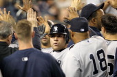Russell Martin of the New York Yankees celebrates in the dugout after scoring on a double by Derek Jeter in the third inning of Game Four of the...