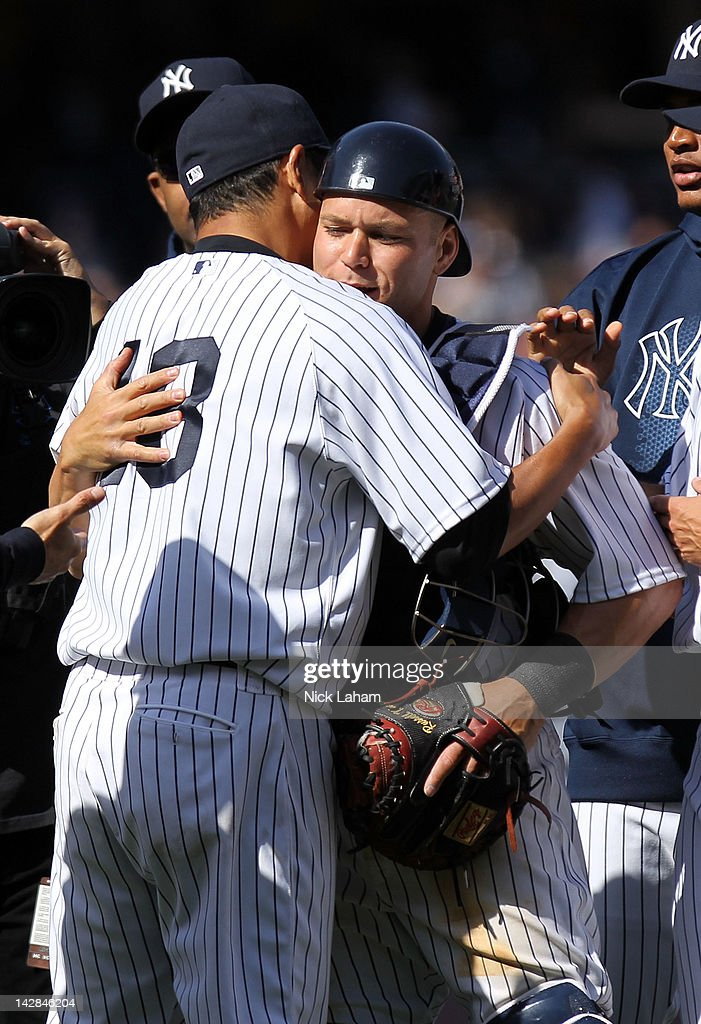 <a gi-track='captionPersonalityLinkClicked' href=/galleries/search?phrase=Russell+Martin+-+Baseball+Player&family=editorial&specificpeople=13764024 ng-click='$event.stopPropagation()'>Russell Martin</a> #55 of the New York Yankees celebrates with <a gi-track='captionPersonalityLinkClicked' href=/galleries/search?phrase=Hiroki+Kuroda&family=editorial&specificpeople=5498664 ng-click='$event.stopPropagation()'>Hiroki Kuroda</a> #18 and manager Joe Girardi #28 after defeating the Los Angeles Angels by a score of 5-0 during the home opener at Yankee Stadium on April 13, 2012 in the Bronx borough of New York City.