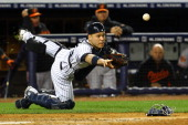Russell Martin of the New York Yankees flips the ball to Hiroki Kuroda of the New York Yankees after a wild pitch during their game against the...