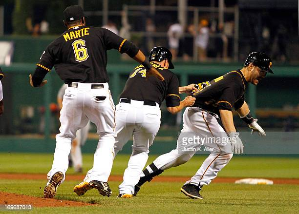 Russell Martin of the Pittsburgh Pirates is mobbed by teammates after hitting an RBI walk off single in the eleventh inning against the Detroit...