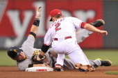 Russell Martin of the Pittsburgh Pirates slides past second base but gets his hand on the base before Zack Cozart of the Cincinnati Reds can tag him...