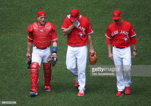 Russell Martin of the Toronto Blue Jays and Joe Biagini and pitching coach Pete Walker make their way from the bullpen to the dugout before the start...
