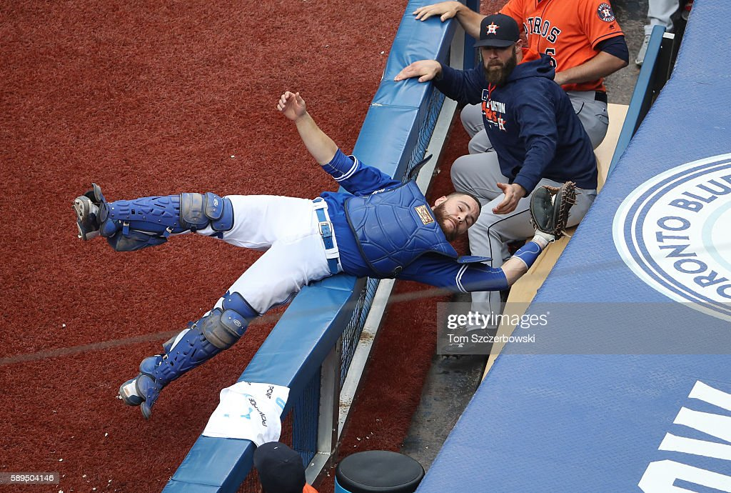 Russell Martin #55 of the Toronto Blue Jays catches a foul pop up in the seventh inning during MLB game action and avoids falling into the Houston Astros dugout on August 14, 2016 at Rogers Centre in Toronto, Ontario, Canada.