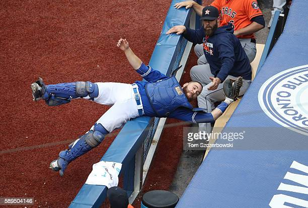 Russell Martin of the Toronto Blue Jays catches a foul pop up in the seventh inning during MLB game action and avoids falling into the Houston Astros...
