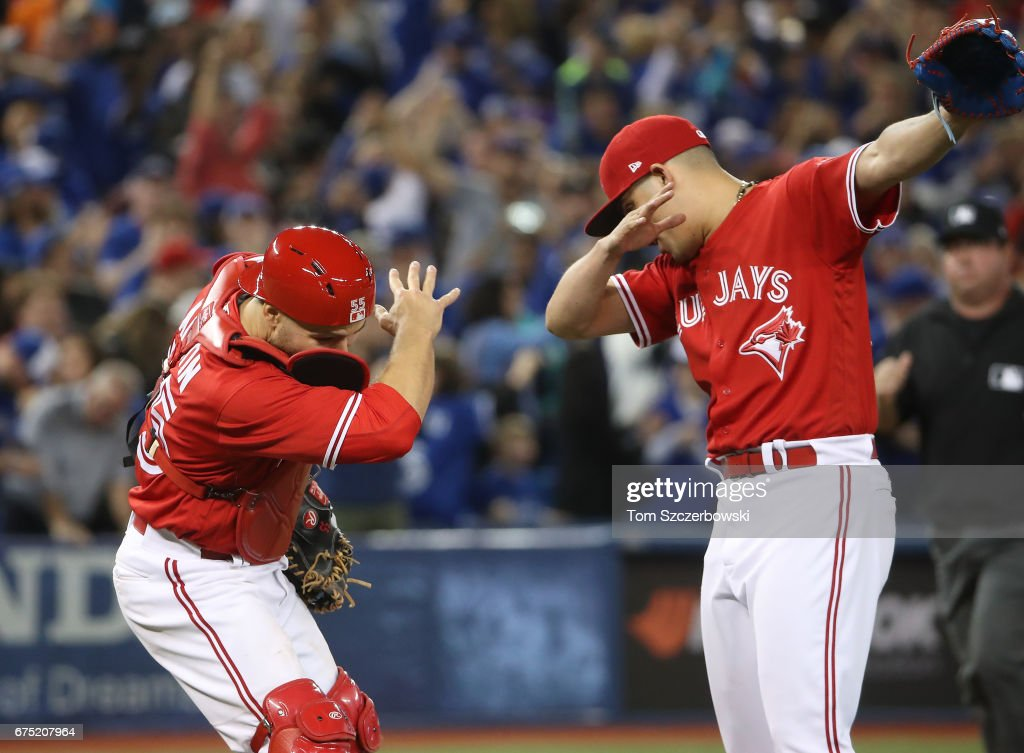 Russell Martin #55 of the Toronto Blue Jays celebrates their victory with Roberto Osuna #54 during MLB game action against the Tampa Bay Rays at Rogers Centre on April 30, 2017 in Toronto, Canada.