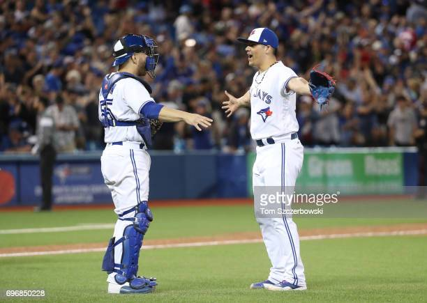Russell Martin of the Toronto Blue Jays celebrates their victory with Roberto Osuna during MLB game action against the Tampa Bay Rays at Rogers...