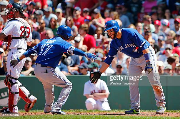 Russell Martin of the Toronto Blue Jays greets Ryan Goins of the Toronto Blue Jays at home after Goins' threerun home run against the Boston Red Sox...