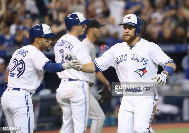 Russell Martin of the Toronto Blue Jays is congratulated by Devon Travis after both runners scored on an RBI single by Darwin Barney in the second...