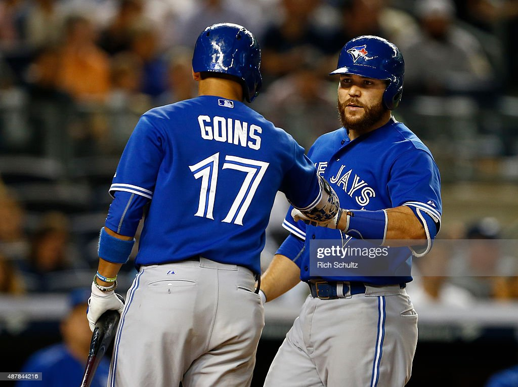 Russell Martin #55 of the Toronto Blue Jays is congratulated by Ryan Goins #17 after hitting a two run home run against the New York Yankees in the seventh inning of a MLB baseball game at Yankee Stadium on September 11, 2015 in the Bronx borough of New York City. The Blue Jays defeated the Yankees 11-5.
