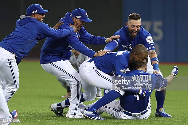 Russell Martin of the Toronto Blue Jays is swarmed by teammates after the Toronto Blue Jays defeated the Texas Rangers 76 in ten innings during game...
