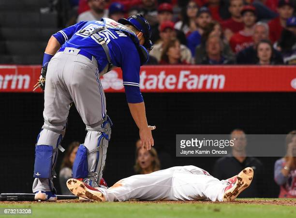 Russell Martin of the Toronto Blue Jays offers a hand to Andrelton Simmons of the Los Angeles Angels of Anaheim after he was knocked down by a pitch...