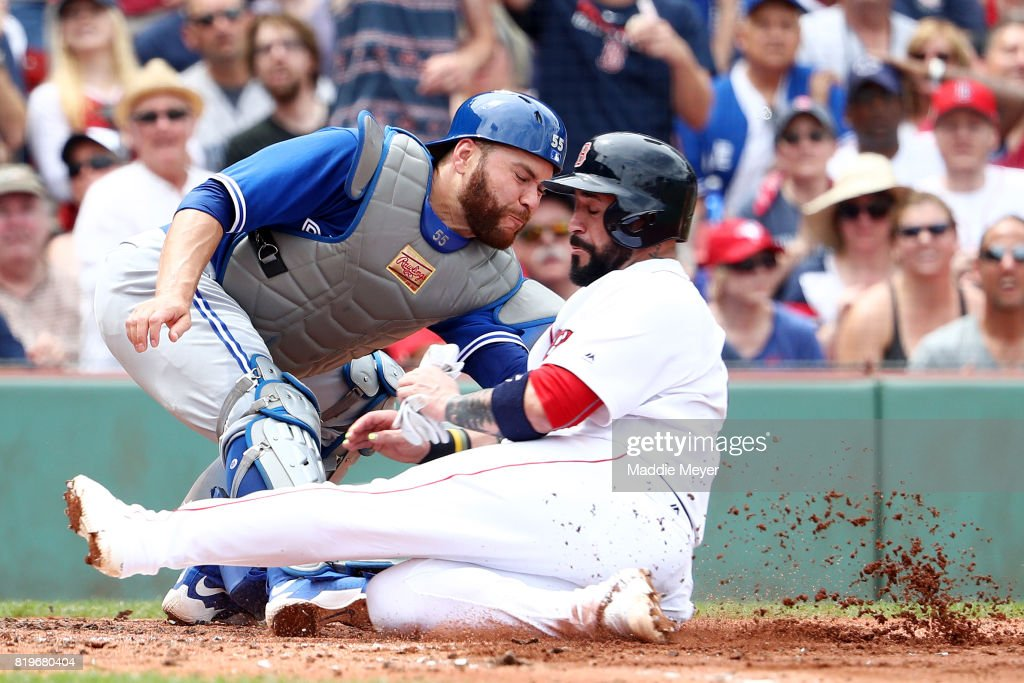 Russell Martin #55 of the Toronto Blue Jays tags out Sandy Leon #3 of the Boston Red Sox at home during the second inning at Fenway Park on July 20, 2017 in Boston, Massachusetts.